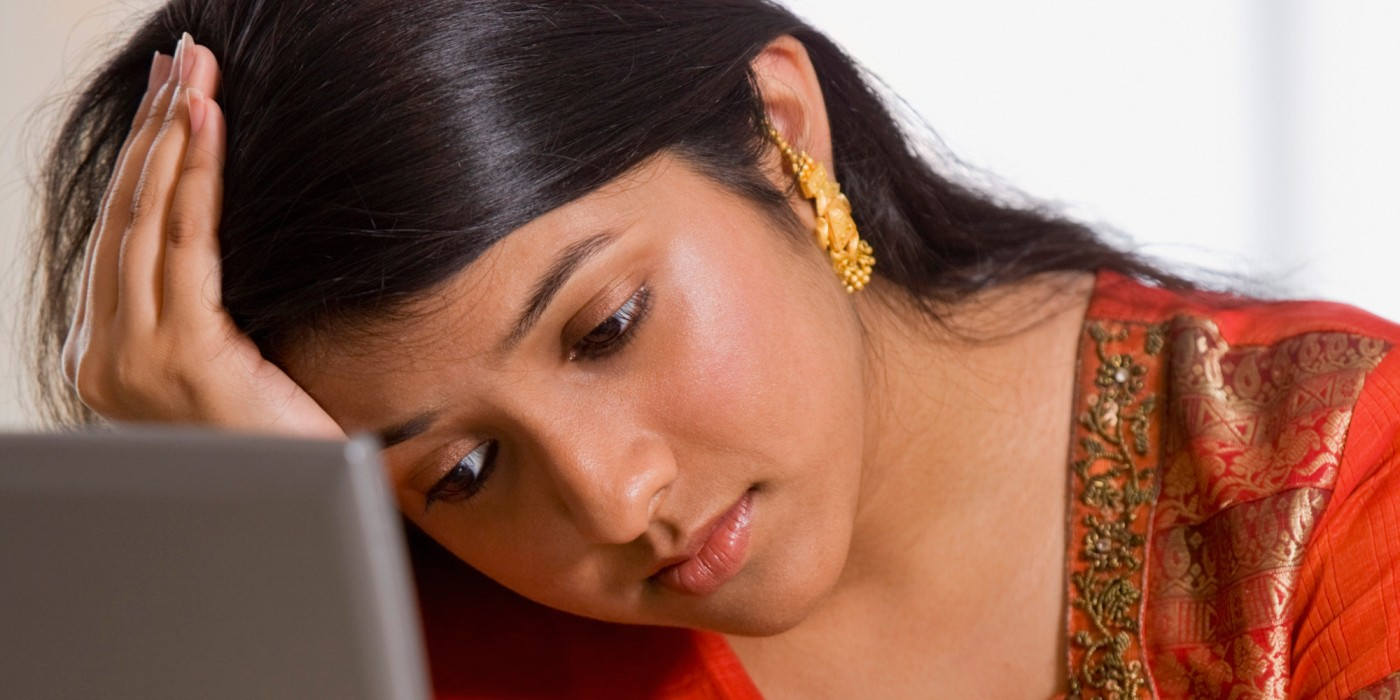 Indian businesswoman resting head in hand